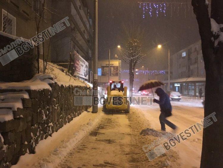 Снеговалежът е обилен и бързо трупа, но тротоарът по главния улевар беше изчистен тази вечер от малка машина