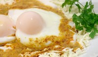Яйца върху червени домати на фурна